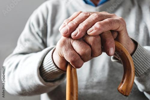 Fotomural Hands of an elderly man resting on a walking cane
