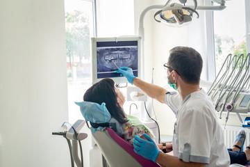 Doktorski dentysta pokazuje pacjenta zęby na promieniowaniu rentgenowskim