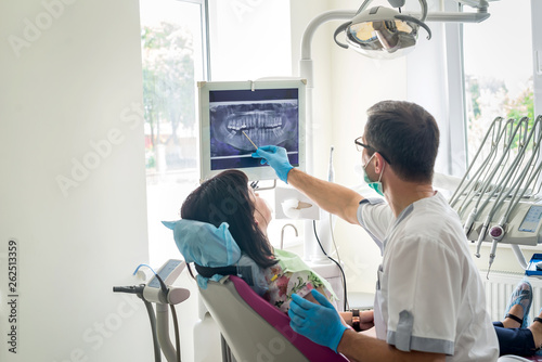 Doctor dentist showing patient's teeth on X-ray