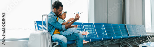 Obraz panoramic shot of african american father and son sitting with suitcase in airport and playing with toy plane - fototapety do salonu