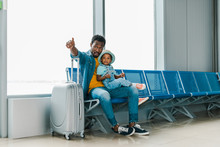 African American Father Sitting With Son In Airport And Pointing With Finger Away