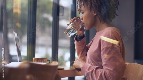 Fotomural  pretty young black woman study working indoor drinking water