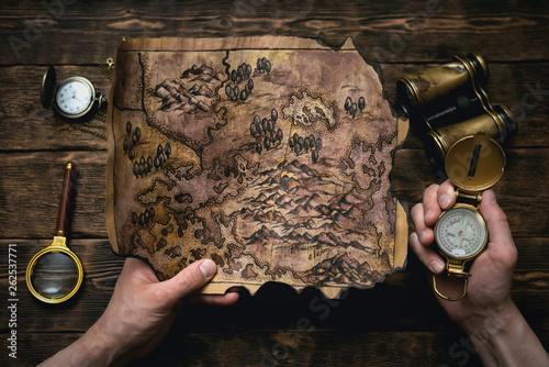 Obraz na plátně Old map in man adventurer hands on a brown table background