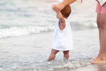 Hand Of Mother Training Baby To Walking First Steps On The Beach