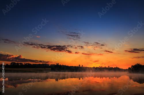 Foto auf Leinwand Blaue Nacht wonderful misty morning. majestic sunrise over the lake. picture