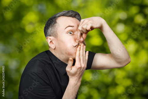 Fotografia, Obraz  Portrait of a young guy with gray hair with feeling sick, who covers his mouth and nose from the stench with nausea