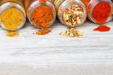 Kolorowe przyprawy wysypujące się ze leżących słoików leżących. Przyprawy i wolna przestrzeń na drewnianym blacie. Liofilizowane warzywa, mielona papryka, curry i mieszanki przypraw.