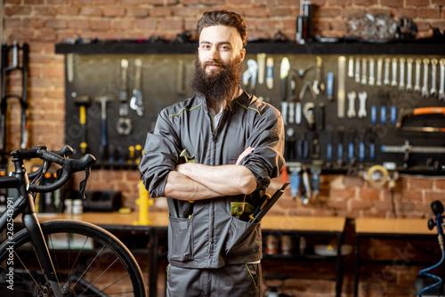 Fototapeta Portrait of a handsome bearded repairman in workwear standing with wrenches at the bicycle workshop obraz