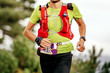 canvas print picture - male athlete run mountain race with hydratation trail vest for running