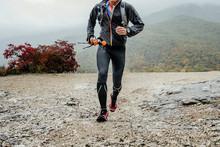 Male Skyrunner Running Mountain Trail With Trekking Poles In Rain