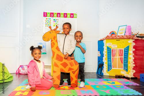 Fototapeta Group of black boys and girl hold drawn giraffe obraz na płótnie