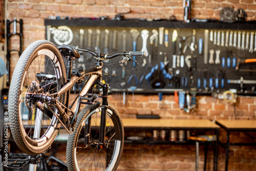 Obraz Mountain bicycle during the repairing process hanging on the stand at the workshop - fototapety do salonu