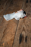 Bandage with tape fallen on wooden floor. - 262568191