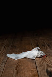 Bandage with tape fallen on wooden floor. - 262568194