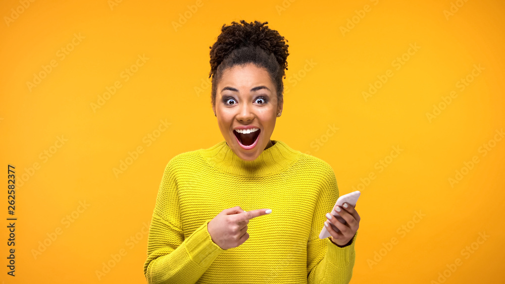 Fototapeta Joyful young woman pointing at smartphone in hand, online shopping application
