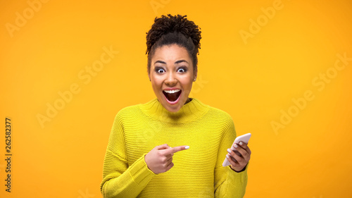 Joyful young woman pointing at smartphone in hand, online shopping application