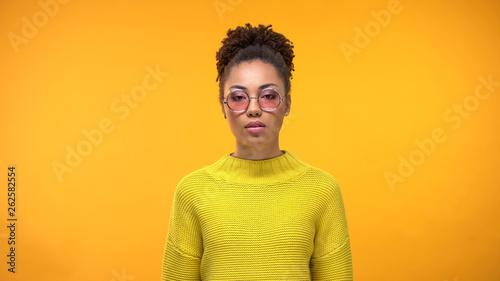 Photographie  Serious young female standing on bright background, style and fashion, outfit