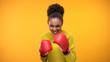 Leinwanddruck Bild - Smiling african teenager in boxing gloves imitating fight, having fun, victory