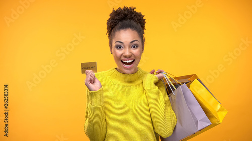 Fotografía  Cheerful woman with shopping bags and golden credit card, rich customer service