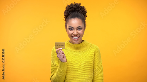 Fotografía  Black woman holding golden credit card, VIP banking programs for rich people