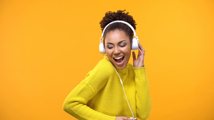 Cheerful afro-american woman in headset enjoying favorite song by radio app