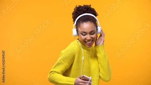 Smiling female listening to favorite melody in white headphones, technology - 262584567