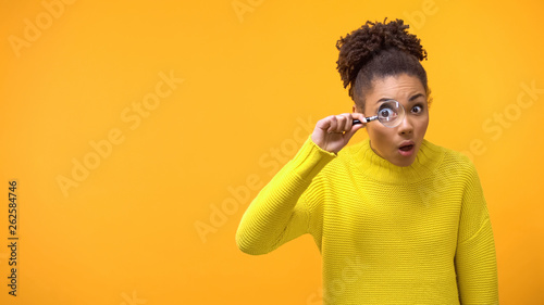 Fotografiet  Teenage female looking magnifying glass, shocked and surprised by information