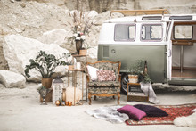 Green Hippy Bus, Vintage Armchair With Pillows, Retro Radio, Golden Metal Decorations With Plants, Succulents, Flowers And Candles, Fur Carpet On The Background Of Desert Landscape. Boho Decor