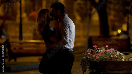 Fotografia  Beautiful couple cuddling and kissing tenderly in park, evening date, love