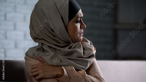 Obraz na płótnie Crying muslim female holding painful hand, suffering from husband violence