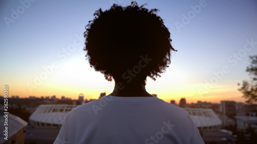 Fotografía  Afro-american curly haired woman enjoying sunset on roof, meditation, back view