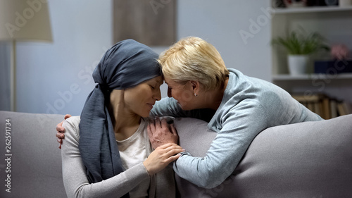 Valokuvatapetti Mother hugging her daughter suffering from cancer, family support, togetherness