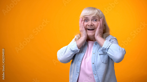 Cheerful surprised elderly lady satisfied with news, discounts and holiday sale Obraz na płótnie