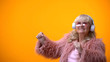 Positive elderly lady in pink coat and round sunglasses listening to music