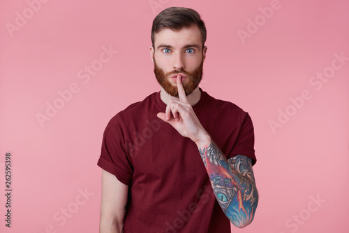 Photo of silent serious calm bearded man with tattooed hand showing