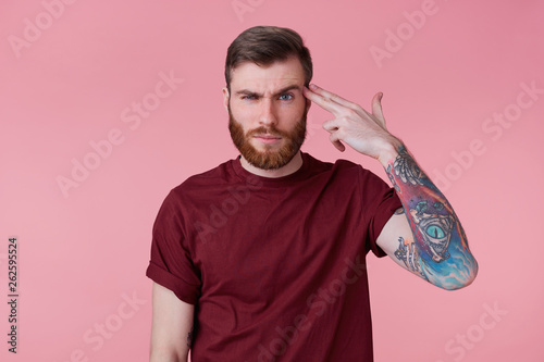 Fotomural Photo of young bearded inked man isolated over pink background, shooting at his head with hand gun, showing suicide gesture