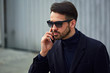 Fashion beard style business handsome male model in fashion sunglasses and blue coat with serious concentrated look talking on mobile phone on wall outdoors background.