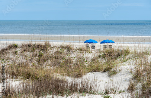 A beachfront view of two blue beach umbrellas and chairs Canvas Print