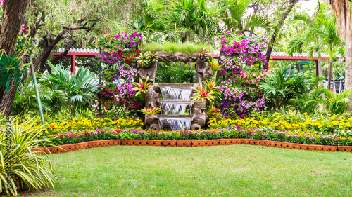 Türaufkleber Gelb Waterfall flows and vivid flowers pot decoration in cozy home flower garden on summer.