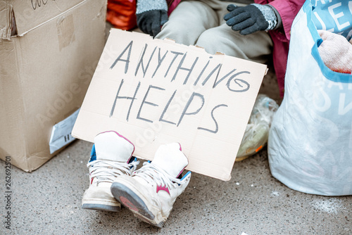 Homeless holding social message on the cardboard, asking money on the street Canvas Print