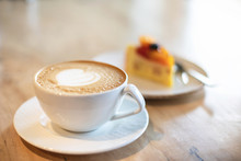 White Cappuccino Cup With With Latte Art Heart And Cake On Light Brown Wood Background Lit By Bright Morning Sunlight