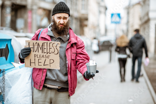 Portrait of a depressed homeless beggar with cardboard begging some money on the Wallpaper Mural