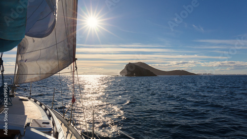 Staande foto Zeilen View over the bow of a sailing yacht to Isla Grosa, La Manga and the Mar Menor with the sun as backlight