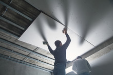 Workers Fitting Panel Into Fra...