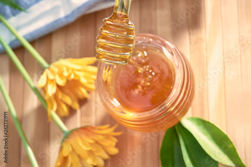 honey dripping from a spoon of honey on bamboo wood.