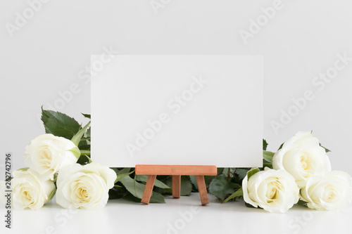 Photo  White card mockup with roses on a white table.