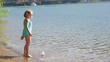 Little Girl Places Her Handmade Paper Boat In Water Then Looks Around