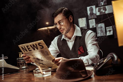 Concentrated detective in glasses reading newspaper in dark office Poster Mural XXL