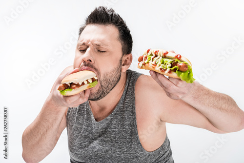 hungry overweight man in tank top eating hot dog isolated on white Canvas Print