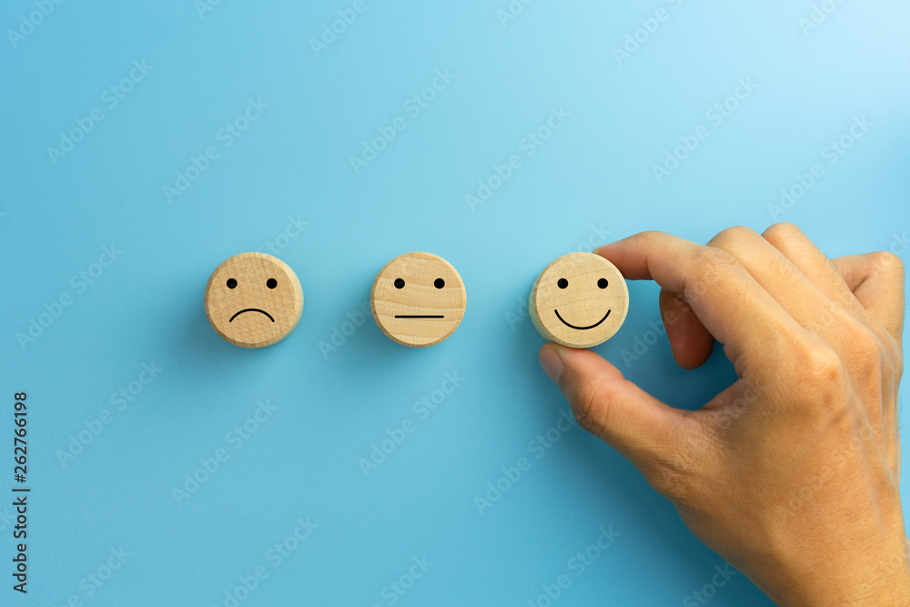Fototapeta Customer service evaluation and satisfaction survey concepts. The client's hand picked the happy face smile face icon on wooden cube on blue background. copy space